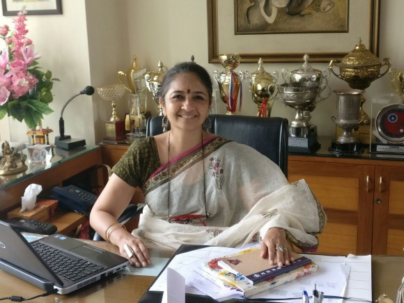 Photo of Mrs. Richa Sharma Agnihotri, the Principal of Sanskriti School, sitting in her office.